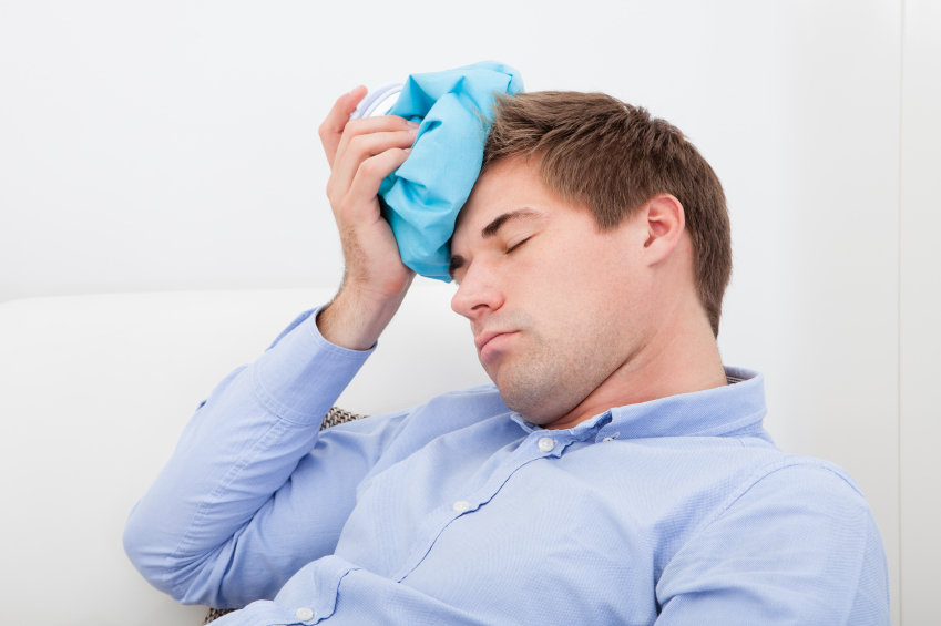 Young Man Suffering With Headache Applying Icepack